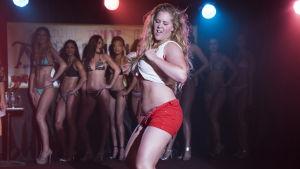 Renée dansar iklädd uppknäppta shorts och kort linne.