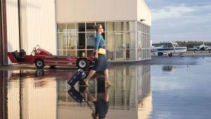 Renée går mot ett flygplan med huvudet högt och kappsäcken käckt på svaj.
