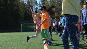 Många barn övar växlingar på en fotbollsplan.