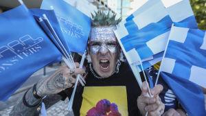 En man med många Finlandsflaggor och Saara Aalto-flaggor visar tänderna.