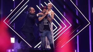 En ordningsvakt försöker fösa ner en person från Eurovisionsscenen medan brittiska Surie ser på.