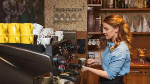 en servitris som häller upp kaffe
