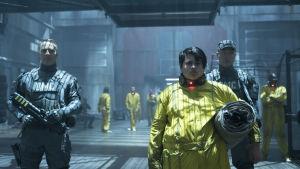 Russell iklädd gul dräkt på väg till sin fängelsecell.
