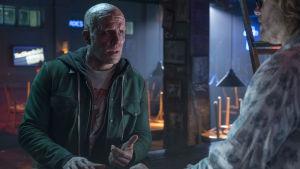Deadpool utan mask förklarar sin situation för sin bartenderkompis Weasel.