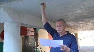 Jaakko Rönkkö sträcker handen mot tunnelns tak med kolkritan i handen, ser på skisspapper i andra handen.