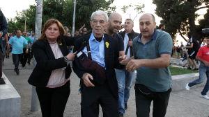 Calypso Goula (till vänster) hjälper bort Yiannis Boutaris (i mitten) från ceremonin i Thessaloniki på lördag kväll.