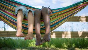 Två barn ligger i en hängmatta.