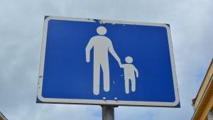 Ett trafikmärke där en vuxen håller ett barn i handen.