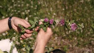Händer som binder en blomsterkrans.