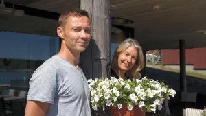 Raine och Pia Kaukiainen står vid en vit blomma på sin terass