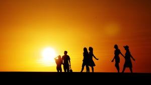 Människosilhuetter mot solnedgång