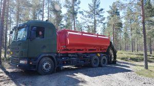 En bild på en tankbil som fungerar som brandbil vid behov. Tankbilen är röd. Runt omkring den finns det tallskog. Tankbilen tillhör Försvarsmakten.