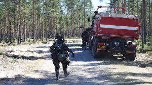 En beväring går längs med en sandig väg i en skog. Beväringen har mycket utrustning på sig och går mot en militärisk brandbil som är röd. Man ser bakändan på bilen.