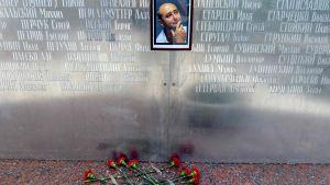 """Blommor vid en minnesvägg nära den """"mördade"""" journalisten Arkadij Babtjenkos tidigare hus i Moskva."""