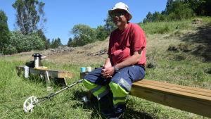En man i röd t-skjorta och arbetsbyxor sitter på en bänk. Han har en metalldetektor med sig och han sitter ute i naturen på ett område där man letar arkeologiska fynd.
