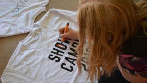 En flicka ritar på en t-tröja