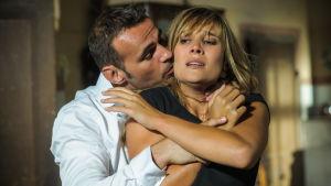 Mies on tarttunut naista takaapäin kiinni ja yrittää suudella. Nainen on hätääntynyt.