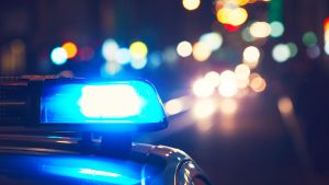 En polisbils blåljus lyser i natten med gatulyktor och billjus i bakgrunden.