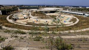 en övergiven kajakstadion i aten. en tom betongränna med hinder i sig. det växer ogräs överallt.