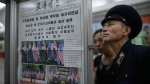 Man i uniform läser väggtidning i Nordkorea, med bilder från toppmötet mellan Trump och Kim Jong-Un