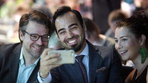 De Grönas riksdagsledamöter Ville Niinistö, Ozan Yanar och Emma Kari tar en selfie på partikongressen i Vanda.