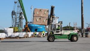 En truck lyfter fram sågat virke i Kaskö hamn.
