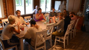 Många glada unga människor sitter kring ett stort matbord i ett kök.