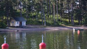 En simstrand med en liten gul stuga. I förgrunden syns röda bojar.