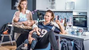 Kaksi naista istuu vauva sylissä keittiössä ja katsoo kameraan. Takana näkyy mm. viinipullo.