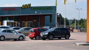 På bilden synns bilar som står parkerade framför en servicestation. Huset har skyltarna Hesburger, ABC och Kuninkaantie.