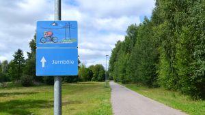 Vägskylt med cyklist och fågelsom flyger bakom cyklisten, står Jernböle på skylten.