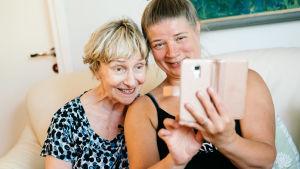 Vanhempi ja nuorempi nainen ottavat yhdessä selfietä.