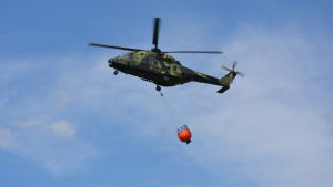 Militärhelikopter med vattenbalja.