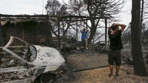 Invånare i Mati inspekterar sitt hus efter branden i Mati.
