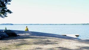 Kvinan i gul skjorta sitter på klippa och tittar ut över havet.