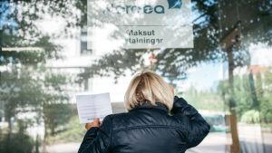 Eläkeikäinen nainen katsoo kiinni olevan pankin ikkunasta paperilasku kädessään.