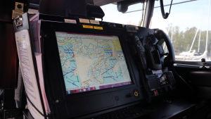 En bild på instrumentbrädan i ett sjöräddningsfartyg. På en skärm ser man en karta.