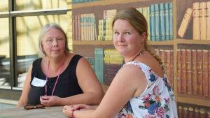 Två kvinnor sitter vid ett träbord. Den ena kvinnan har vänt sig om mot kameran så att man ser hennes rygg och den andra kvinnan sitter rakt i riktning mot kameran