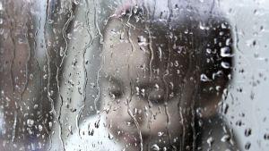 ett litet barn bakom ett fönster i regn