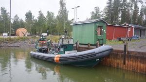 Liten sjöbevakningsbåt vid brygga