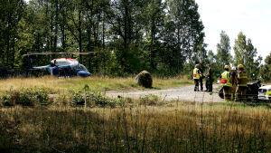 En polishelikopter, poliser, räddningspersonal och militärer nära platsen för Jas-haveriet i Blekinge den 21 augusti 2018