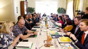 Regeringspolitiker sitter vid ett somrigt långbord fotograferat från ena ändan.