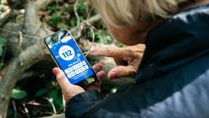 Kuvassa vanhus on metsässä ja avaa kännykästä 112-sovelluksen