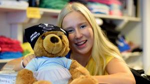 """En blond ung kvinna ler och håller i en nalle som har en duk på huvudet där det står """"Hurja Piruetti""""."""