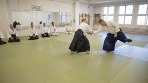 Kikka Niittyaho ja opettaja Harri Rautila näyttävät salin keskellä seuraavan harjoituksen esimerkkinä muille.