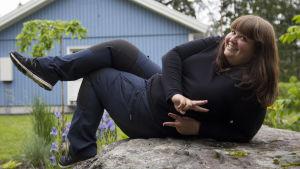 Trädgårdsmästaren Kristine Vesterlund halvligger på en sten och poserar.