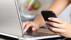 Kvinna som sitter framför en bärbar dator med en smarttelefon i handen.