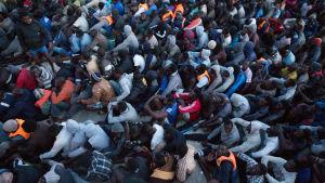 Flyktingar som den libyska kustbeavkningen har räddat ur Medelhavet väntar på att föras till interneringsläger