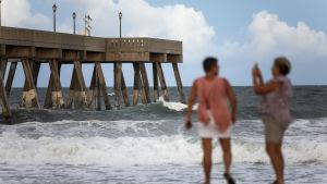 Folk fortograferar de stora vågorna vid en strand i North Carolina.