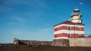 Punavalkoraidallinen majakkarakennus ja ympäröivä muuri.